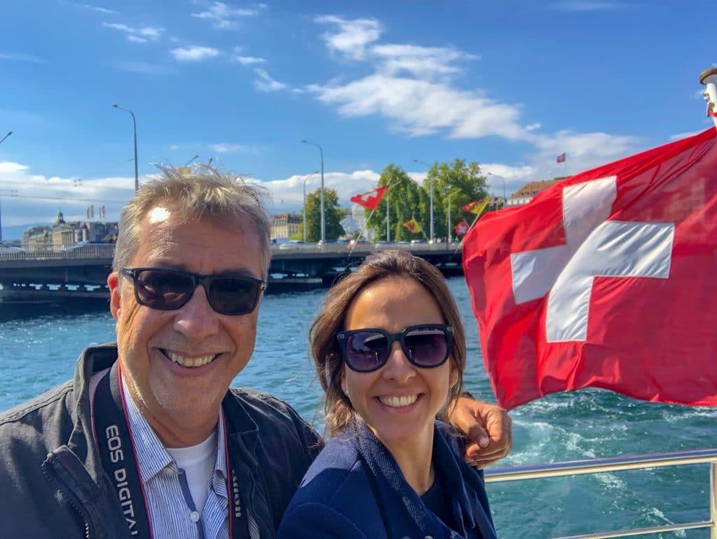 Homem e mulher abraçados dentro de barco perto de bandeira da Suíça