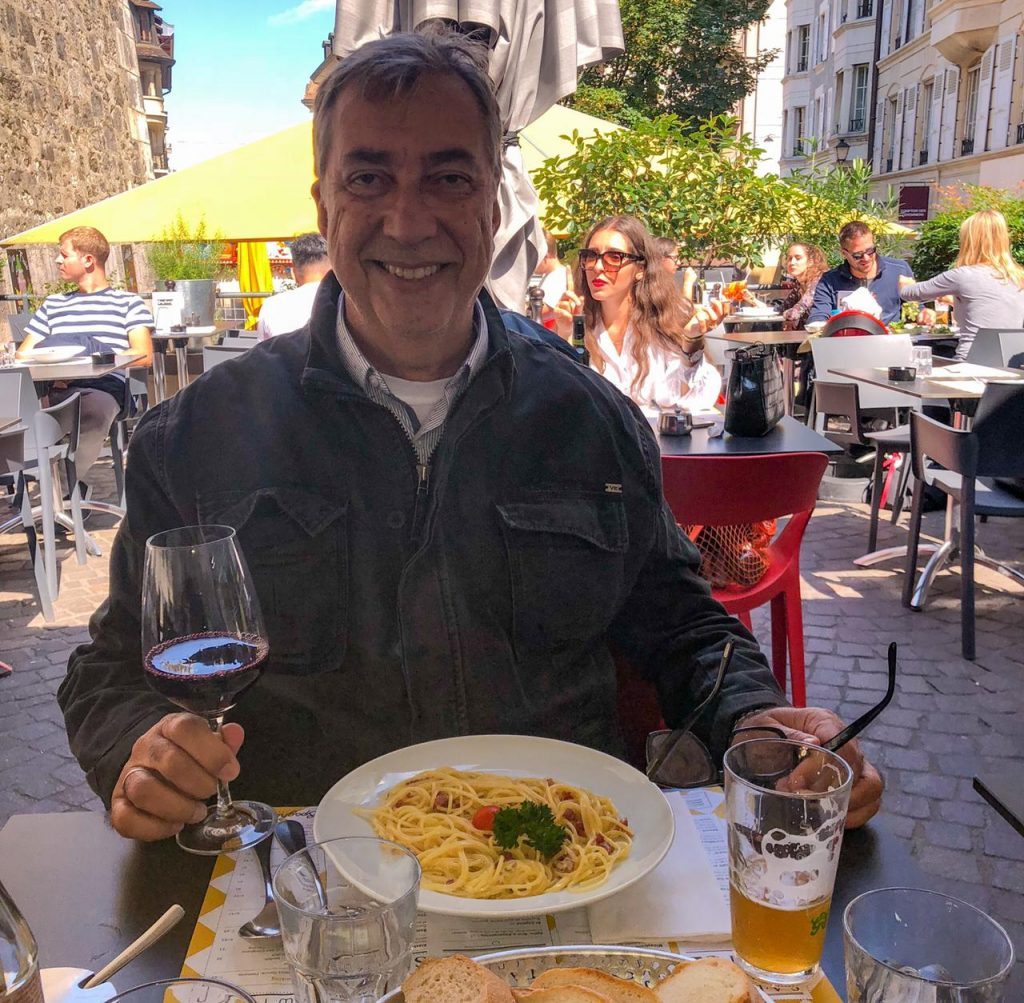 Homem sentado com taça de vinho na mão em restaurante em Genebra