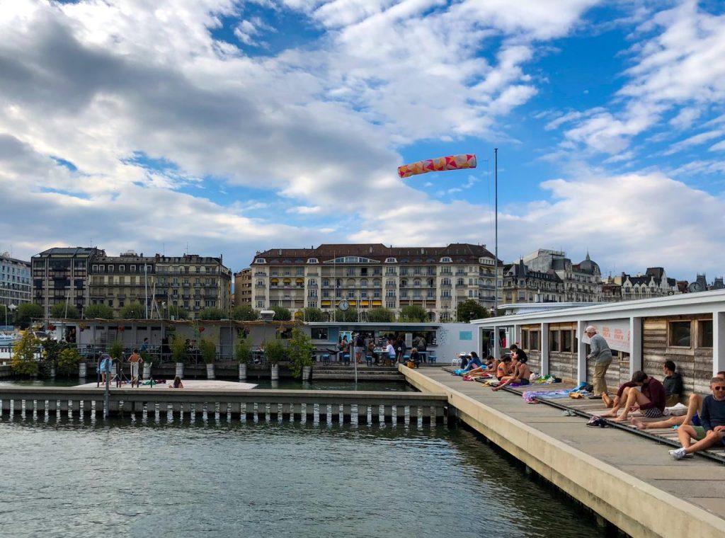 pessoas sentadas tomando sol no Bains de Pâquis em Genebra