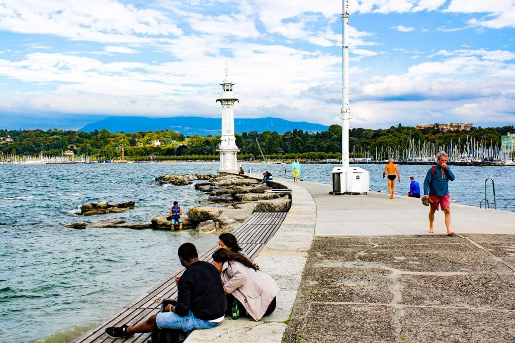 Píer com pessoas sentadas e caminhando na beira do lago Genebra
