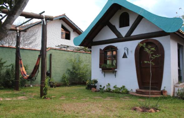 Casa de telhado azul e porta de madeira com rede na varanda