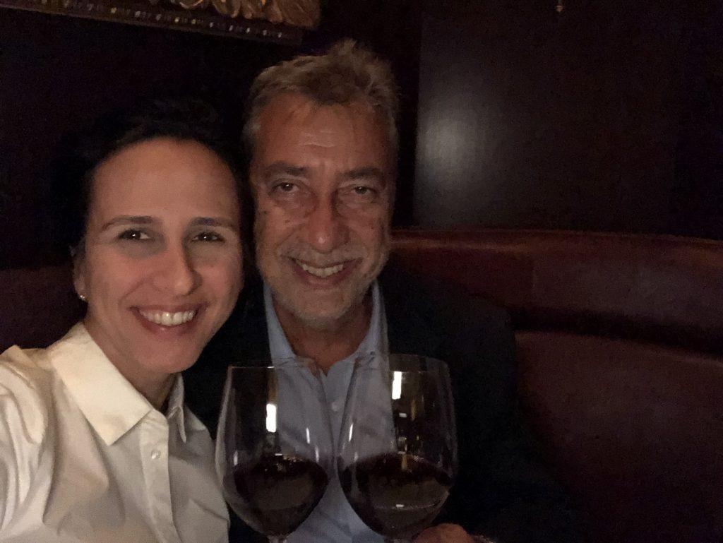 Casal brindando com vinho e sorrindo em restaurante em Miami
