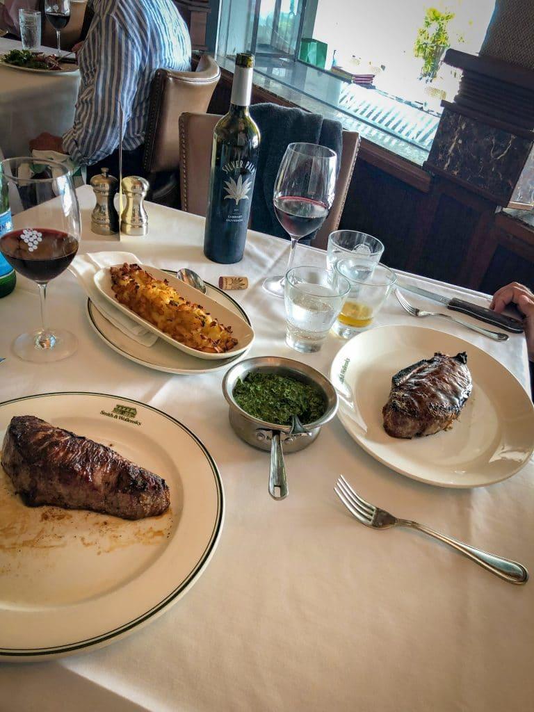 Mesa com duas carnes, vinhos e alguns acompanhamentos em Miami