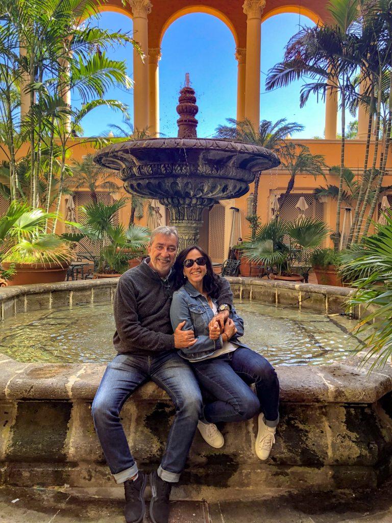 Casal sentado e abraçado em frente a fonte de restaurante em Miami