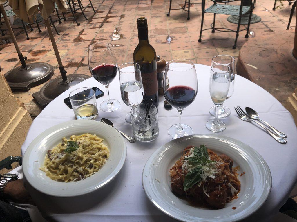 Mesa com dois pratos de comida e taças de vinho cheias em Miami