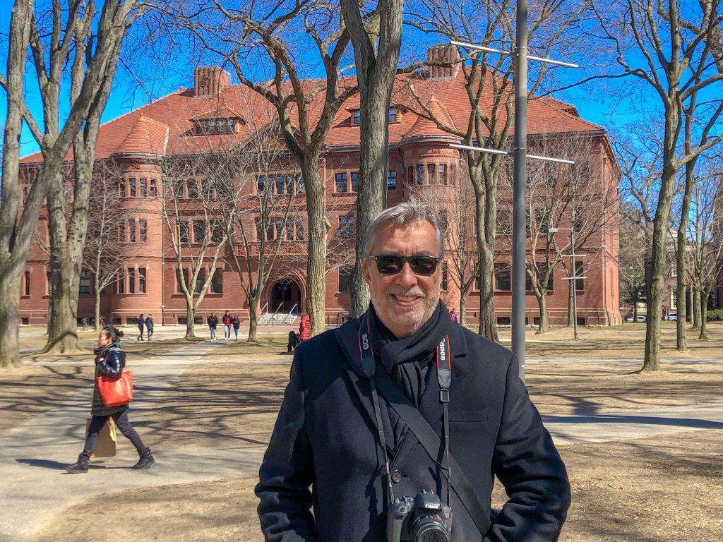 Homem com máquina fotográfica em frente a prédio em Cambridge