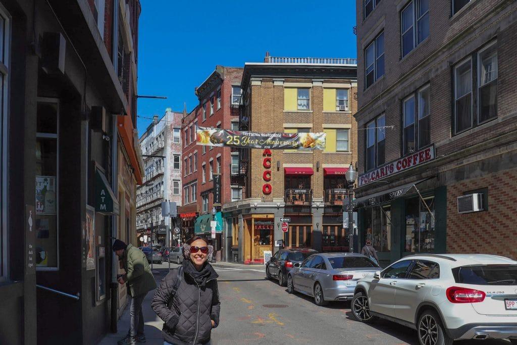 Mulher sorrindo em frente a restaurante no North End, em Boston