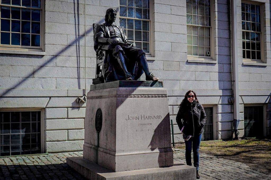 Mulher ao lado de estátua de John Harvard em Cambridge