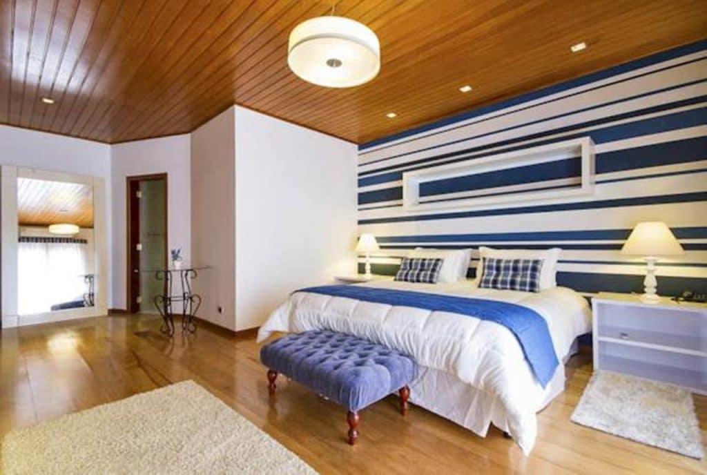 Quarto da pousada com cama de casal, parede colorida e mesas de cabeceira com abajur.