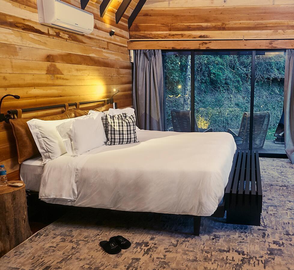 Quarto do hotel com cama e vista para a mata