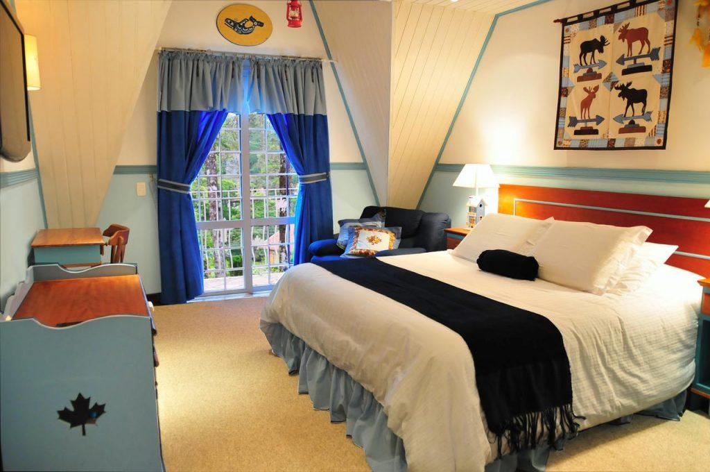 Quarto com cama de casal, poltrona e cortinas azuis