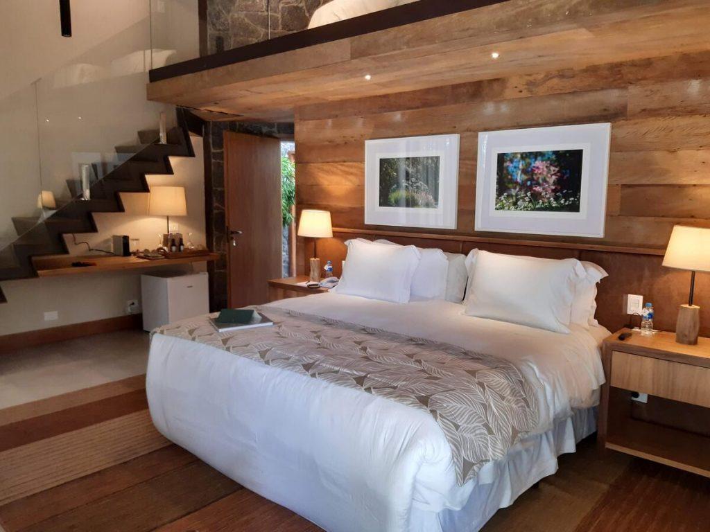 Quarto do hotel com cama grande, frigobar e quadros na parede