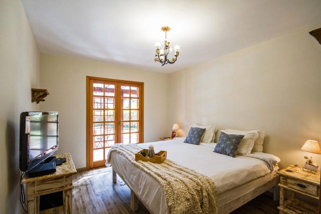 Quarto com cama de casal, cabeceiras e televisão em Campos do Jordão