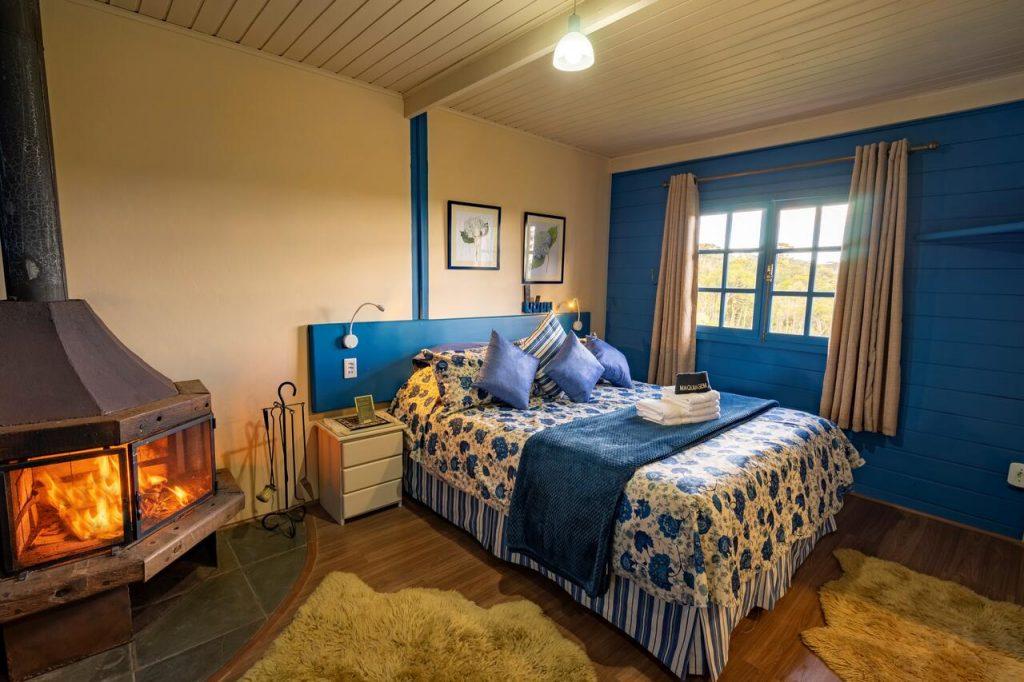 Quarto com lareira acesa e cama toda coberta com colcha azul