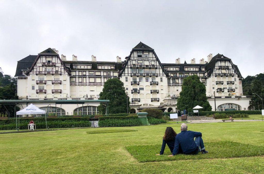 Casal sentado no gramado em frente ao Palácio Quitandinha