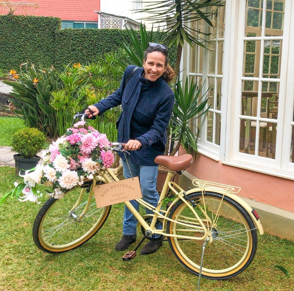 Mulher em frente a uma bicicleta com flores