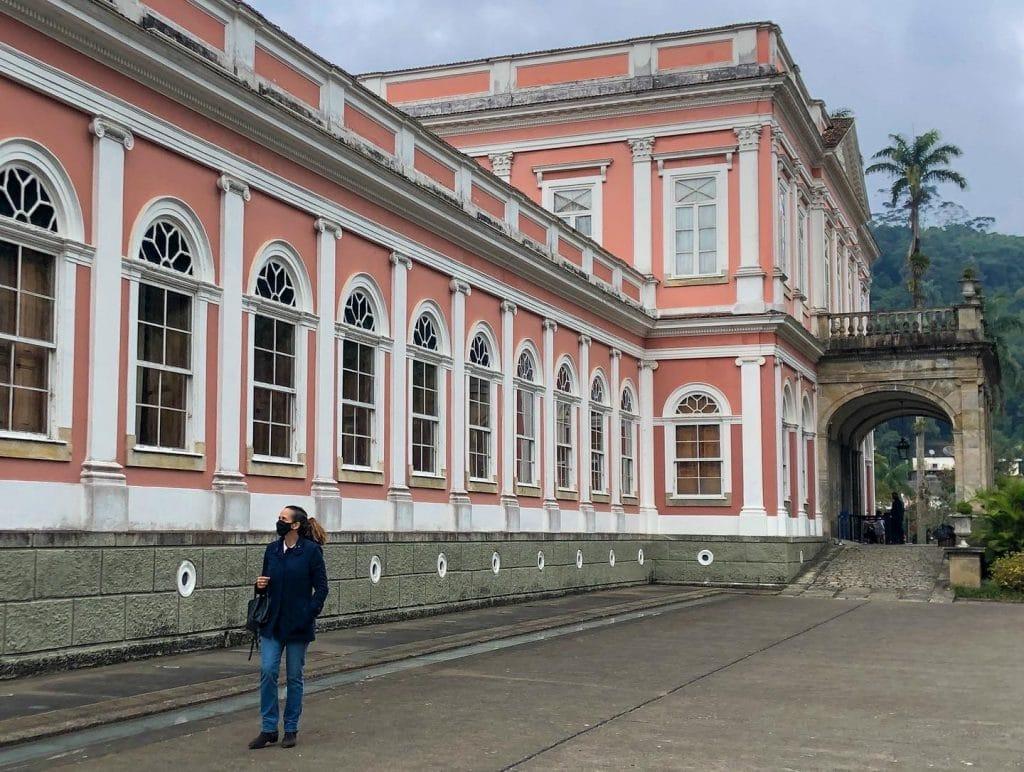 Mulher de máscara caminhando em frente a Museu Imperial