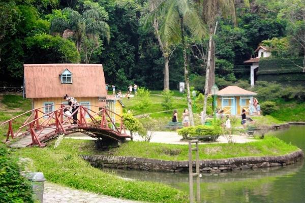 Parque Cremerie em Petrópolis com lago, ponte vermelha e casinhas amarelas