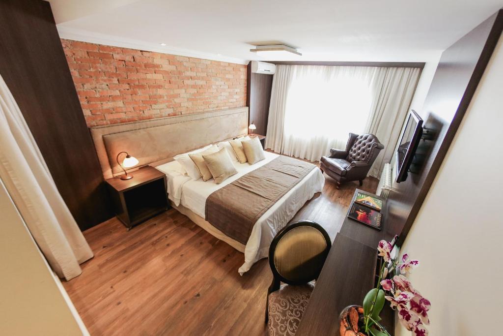 Quarto de hotel em Gramado com cama e poltrona