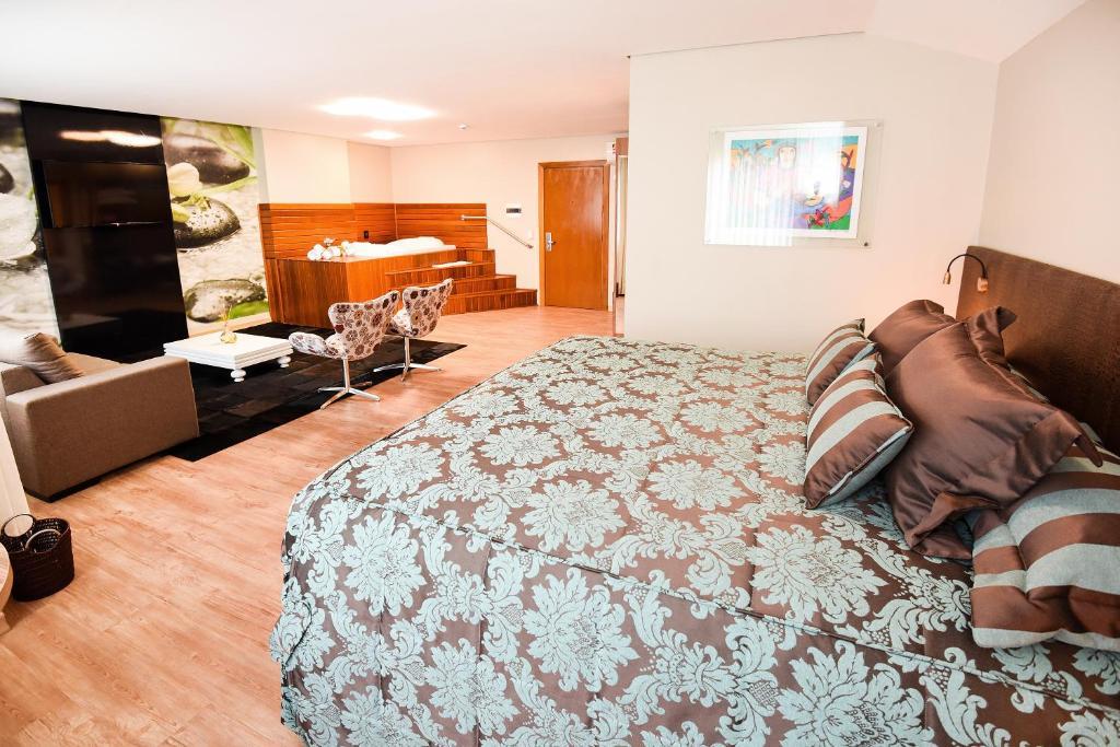 Quarto com cama grande e área de lazer com sofá e poltronas